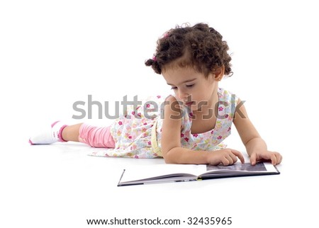 Cute child reading a book on white .