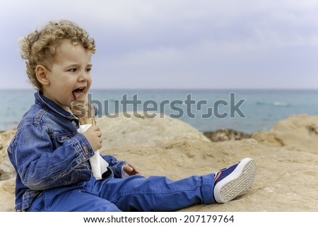 cute child sitting near the beach is eating a chocolate ice cream cone - focus on the child - focus on the child - stock photo