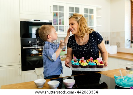 Cute child thankful to mother while preparing cookies in kitchen - stock photo