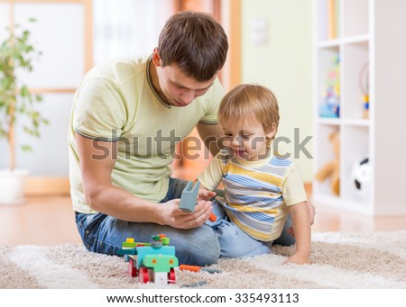 Cute child toddler boy and his father repair toy car at home