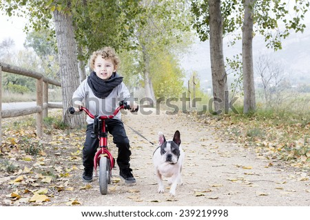 cute child walking his white and black french bulldog riding his bike by a path at the countryside