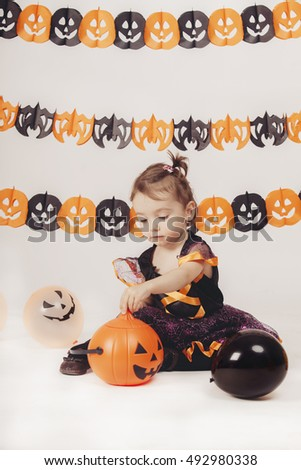 cute child witch playing with halloween decoration