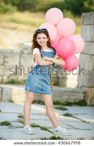Cute child with balloons outdoor, happy girl having fan  summer, fashion kid in jeans dress at street