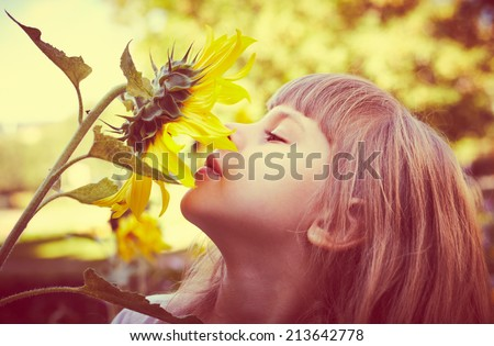 Cute child with sunflower in summer field - stock photo