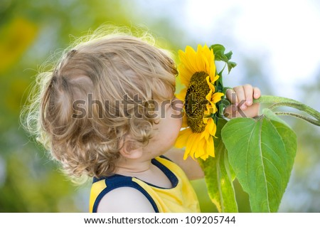Cute child with sunflower on sunny-green background - stock photo