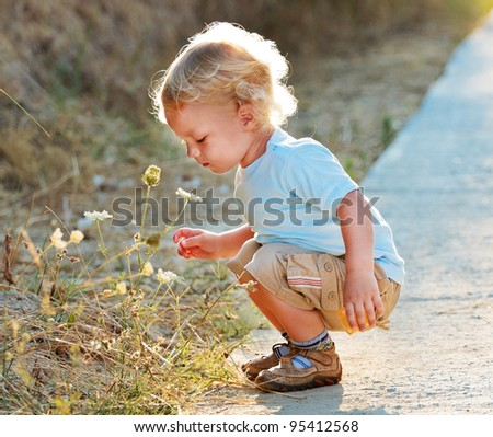 Cute child with wildflowers in sun back light - stock photo