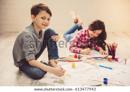 Cute children are painting and smiling while lying on the floor at home