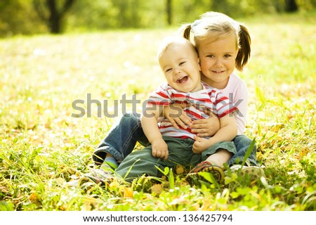 Cute children are playing in autumn park - stock photo