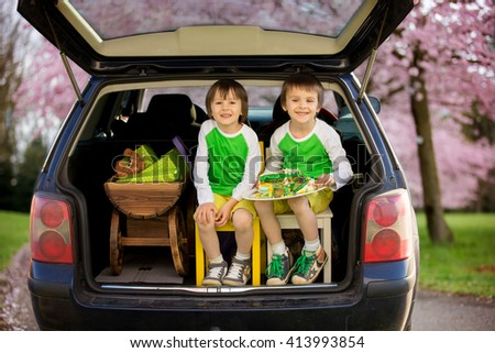 Cute children, boy brothers, sitting in car trunk, holding the leftovers of a birthday cake, trolley with presents in the car, sitting on little chairs, smiling happily after a birthday party - stock photo