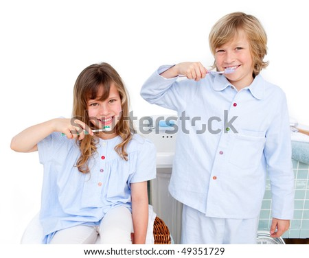 Cute children brushing their teeth at home - stock photo