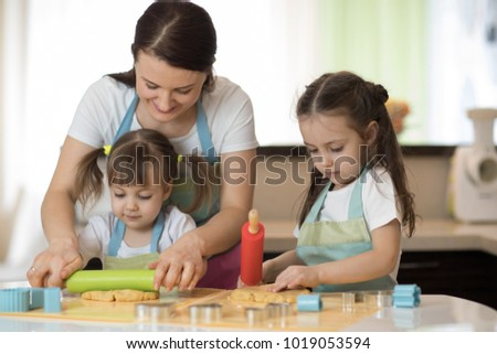 Cute children girls and their beautiful mom in aprons are playing and laughing while kneading the dough in the kitchen