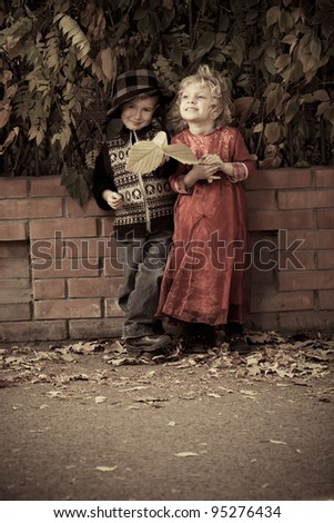 Cute children having a rest at a park. Retro style. - stock photo