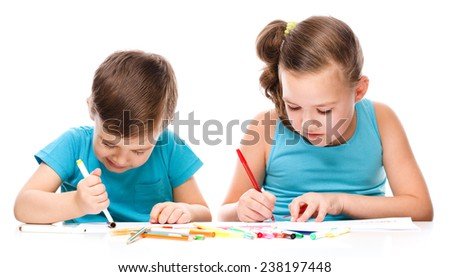 Cute children is drawing on white paper using color pencils
