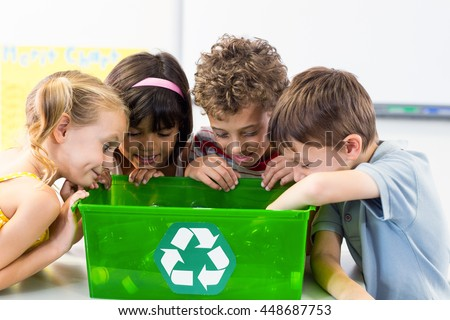 Cute children looking at plastic bottles in recycling box in classroom