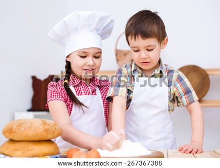 Cute children making bread in the kitchen - stock photo
