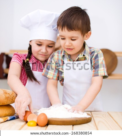 Cute children making bread in the kitchen