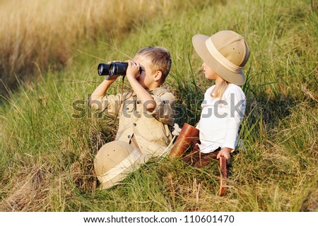 cute children playing pretend safari game together outdoors. happy brother and sister