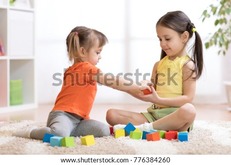 Cute children playing while sitting on carpet at home or kindergarten