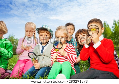Cute children sit in the meadow with magnifiers - stock photo