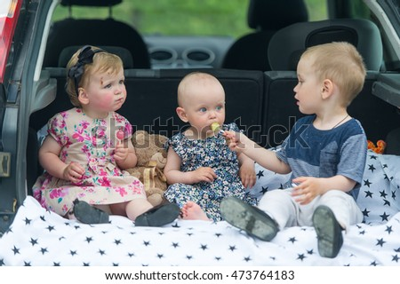Cute children sitting in car trunk. Three kids eat candies.
