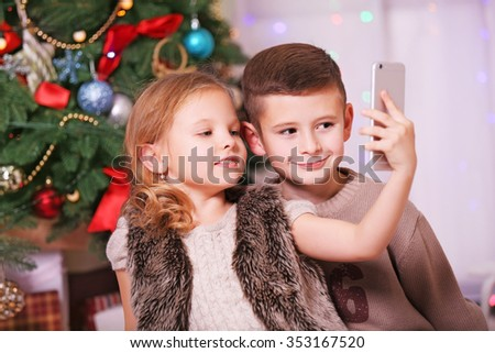 Cute children take selfie in the decorated Christmas room