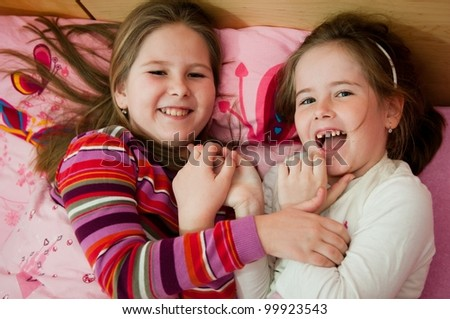 Cute children (two sisters) laughing at home lying in bed