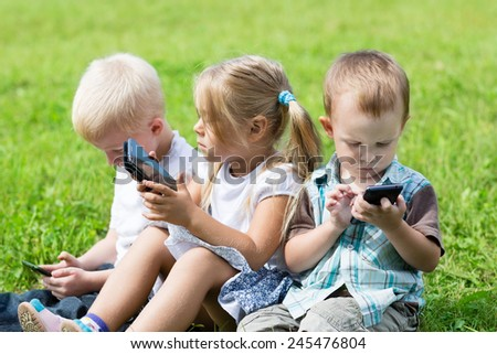 Cute children using smartphones sitting on the grass in the park. Brothers and sister. - stock photo