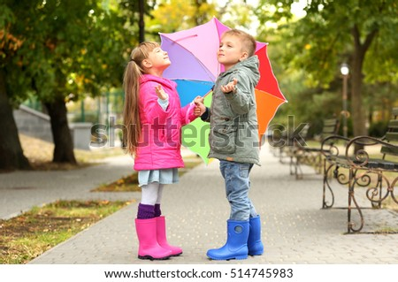 Cute children with umbrella in park