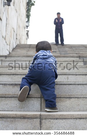 Cute Chinese baby boy crawling on stairs, encouraged by his father, real people - stock photo