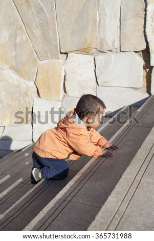 Cute Chinese baby boy crawling on stairs outdoors, shot in Beijing, China - stock photo