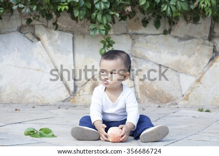 Cute Chinese baby boy eating an apple, shot in Beijing, China - stock photo