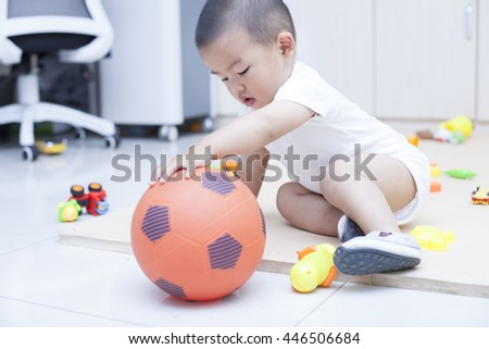 Cute Chinese baby boy playing a soccer ball indoors, shot in Beijing, China - stock photo