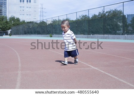 Cute Chinese baby boy playing in a stadium, Beijing, China
