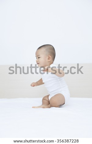 Cute Chinese baby boy playing in bed, hot in Beijing, China - stock photo