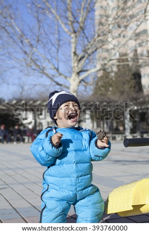 Cute Chinese baby boy playing seesaw outdoors, shot in Beijing, China - stock photo