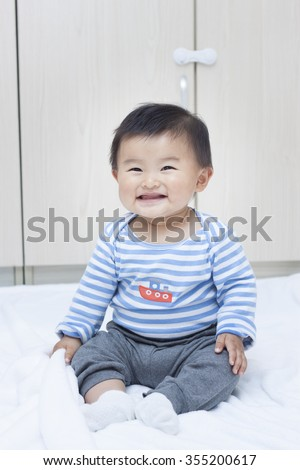 Cute Chinese baby boy sitting on a white blanket, shot in Beijing, China