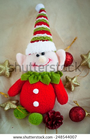cute Christmas elf surrounded by Christmas toys