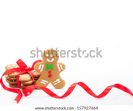 Cute Christmas gingerbread cookies tied with red ribbon on white. - stock photo