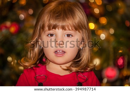 Cute Christmas girl with the Christmas tree in the background - stock photo