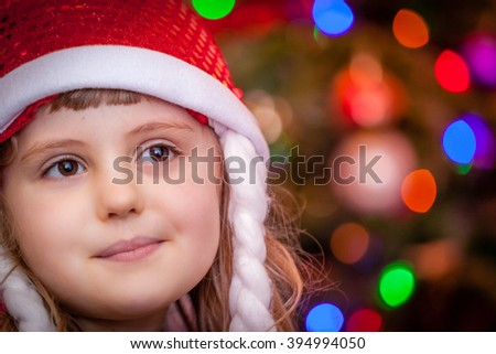 Cute Christmas girl with the Christmas tree lights bokeh in the background - stock photo