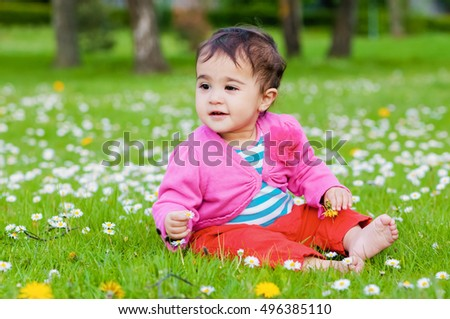 Cute chubby toddler sitting on the grass smiling exploring nature outdoors in the park