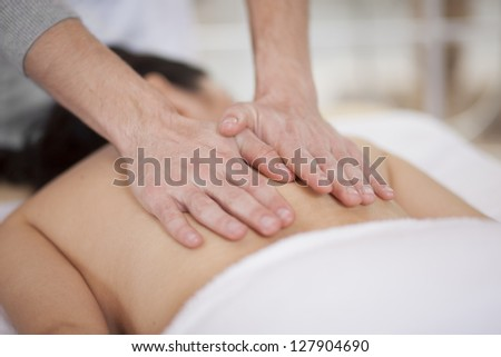 Cute chubby woman getting a back massage at a spa - stock photo