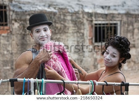 Cute cirque clowns fitting pink coat outdoors - stock photo