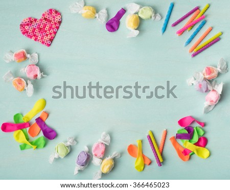 Cute, Colorful Aerial View of a Kids Birthday Heart, Candles, Candy and Balloons around edges on a Cyan Painted Board Background with center room or space for copy, text, your words.  Horizontal