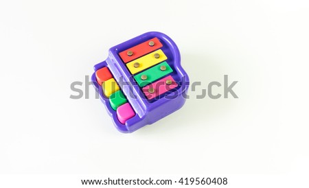 Cute colorful mini piano. Isolated on white background. Slightly de-focused and close-up shot. Copy space.