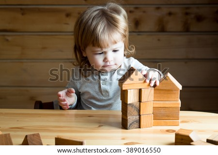 Cute concentrated small baby boy with long blonde curly hair playing and building toy house from wooden blocks indoor, horizontal picture - stock photo
