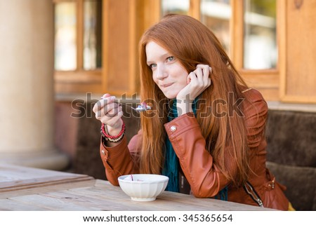 Cute content young woman with beautiful long red hair having breakfast in outdoor cafe and talking on cellphone biting bottom lip - stock photo