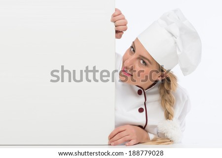 Cute cook chef looking at the camera while holding white menu card board - stock photo