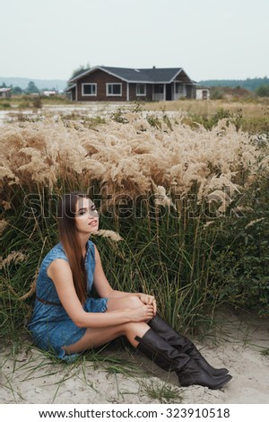 Cute countryside lady with brown hair posing against ranch house. She sits in tall grass against rural scape. She wears jeans dress.   - stock photo