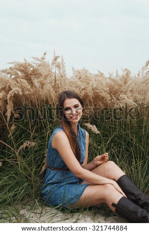 Cute countryside lady with brown hair posing against tall grass. She sits in tall grass against rural scape. She wears jeans dress. Grass is green and yellow. - stock photo